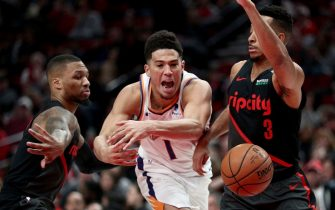 PORTLAND, OR - MARCH 09: Devin Booker #1 of the Phoenix Suns loses the ball against Damian Lillard #0 (L) and CJ McCollum #3 of the Portland Trail Blazers in the third quarter during their game at Moda Center on March 9, 2019 in Portland, Oregon. NOTE TO USER: User expressly acknowledges and agrees that, by downloading and or using this photograph, User is consenting to the terms and conditions of the Getty Images License Agreement.  (Photo by Abbie Parr/Getty Images)