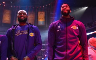 LOS ANGELES, CA - OCTOBER 16: LeBron James #23 and Anthony Davis #3 of the Los Angeles Lakers stand for the National Anthem prior to a pre-season game against the Golden State Warriors on October 16, 2019 at STAPLES Center in Los Angeles, California. NOTE TO USER: User expressly acknowledges and agrees that, by downloading and/or using this Photograph, user is consenting to the terms and conditions of the Getty Images License Agreement. Mandatory Copyright Notice: Copyright 2019 NBAE (Photo by Andrew D. Bernstein/NBAE via Getty Images)