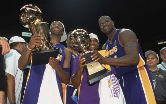 EAST RUTHERFORD, NJ - JUNE 12:  Guard Kobe Bryant #8 of the Los Angeles Lakers holds up the championship trophy as center Shaquille O'Neal #34 hands his Finals Series MVP trophy to guard Lindsey Hunter #10 after winning Game Four of the 2002 NBA Finals against the New Jersey Nets at Continental Airlines Arena in East Rutherford, New Jersey on June 12, 2002. The Lakers defeated the Nets 113-107 and won the series 4-0. NOTE TO USER: User expressly acknowledges and agrees that, by downloading and/or using this Photograph, User is consenting to the terms and conditions of the Getty Images License Agreement Mandatory Copyright Notice: Copyright 2002 NBAE (Photo by Nathaniel S. Butler/NBAE via Getty Images)