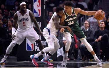 LOS ANGELES, CALIFORNIA - NOVEMBER 06:  Giannis Antetokounmpo #34 of the Milwaukee Bucks back down Patrick Beverley #21 of the LA Clippers as Montrezl Harrell #5 looks on during the first half at Staples Center on November 06, 2019 in Los Angeles, California. (Photo by Harry How/Getty Images)  NOTE TO USER: User expressly acknowledges and agrees that, by downloading and or using this photograph, User is consenting to the terms and conditions of the Getty Images License Agreement.
