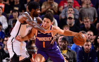 PHOENIX, AZ - NOVEMBER 10: Devin Booker #1 of the Phoenix Suns handles the ball against Kyrie Irving #11 of the Brooklyn Nets on November 10, 2019 at Talking Stick Resort Arena in Phoenix, Arizona. NOTE TO USER: User expressly acknowledges and agrees that, by downloading and or using this photograph, user is consenting to the terms and conditions of the Getty Images License Agreement. Mandatory Copyright Notice: Copyright 2019 NBAE (Photo by Barry Gossage/NBAE via Getty Images)