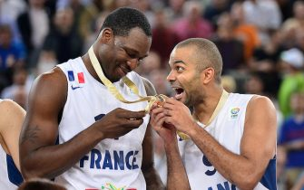 French players Tony Parker (R) and Florent Pietrus celebrate with their medals after winning the EuroBasket championships basketball final match between France and Lithuania in Ljubljana, on September 22, 2013. France won 80 to 66. AFP PHOTO JURE MAKOVEC        (Photo credit should read Jure Makovec/AFP via Getty Images)