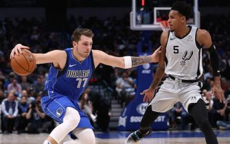 DALLAS, TEXAS - NOVEMBER 18:  Luka Doncic #77 of the Dallas Mavericks dribbles the ball against Dejounte Murray #5 of the San Antonio Spurs in the first half at American Airlines Center on November 18, 2019 in Dallas, Texas.  NOTE TO USER: User expressly acknowledges and agrees that, by downloading and or using this photograph, User is consenting to the terms and conditions of the Getty Images License Agreement. (Photo by Ronald Martinez/Getty Images)
