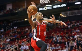 HOUSTON, TEXAS - NOVEMBER 18: Damian Lillard #0 of the Portland Trail Blazers drives past Austin Rivers #25 of the Houston Rockets for a layup during the first quarter at Toyota Center on November 18, 2019 in Houston, Texas. NOTE TO USER: User expressly acknowledges and agrees that, by downloading and/or using this photograph, user is consenting to the terms and conditions of the Getty Images License Agreement.  (Photo by Bob Levey/Getty Images)