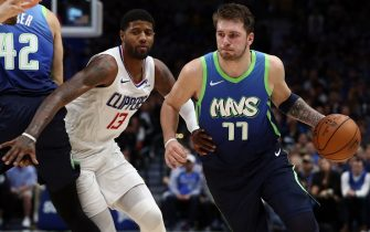 DALLAS, TEXAS - NOVEMBER 26:  Luka Doncic #77 of the Dallas Mavericks dribbles the ball against Paul George #13 of the Los Angeles Clippers at American Airlines Center on November 26, 2019 in Dallas, Texas.  NOTE TO USER: User expressly acknowledges and agrees that, by downloading and or using this photograph, User is consenting to the terms and conditions of the Getty Images License Agreement.  (Photo by Ronald Martinez/Getty Images)