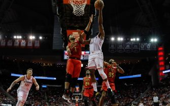 HOUSTON, TX - NOVEMBER 30:  James Harden #13 of the Houston Rockets goes up for a lay up defended by Evan Turner #1 of the Atlanta Hawks and DeAndre' Bembry #95 in the second half at Toyota Center on November 30, 2019 in Houston, Texas.  NOTE TO USER: User expressly acknowledges and agrees that, by downloading and or using this photograph, User is consenting to the terms and conditions of the Getty Images License Agreement.  (Photo by Tim Warner/Getty Images)