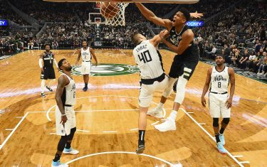MILWAUKEE, WISCONSIN - DECEMBER 06:  Giannis Antetokounmpo #34 of the Milwaukee Bucks dunks over Ivica Zubac #40 of the Los Angeles Clippers during the second half of a game at Fiserv Forum on December 06, 2019 in Milwaukee, Wisconsin. NOTE TO USER: User expressly acknowledges and agrees that, by downloading and or using this photograph, User is consenting to the terms and conditions of the Getty Images License Agreement.  (Photo by Stacy Revere/Getty Images)