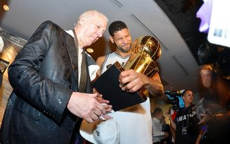 SAN ANTONIO, TX - JUNE 15: Head Coach Gregg Popovich and Tim Duncan #21 of the San Antonio Spurs celebrate in the locker room with the Larry O'Brien trophy after defeating the Miami Heat to win the 2014 NBA Finals in Game Five of the 2014 NBA Finals on June 15, 2014 at AT&T Center in San Antonio, Texas. NOTE TO USER: User expressly acknowledges and agrees that, by downloading and or using this photograph, User is consenting to the terms and conditions of the Getty Images License Agreement. Mandatory Copyright Notice: Copyright 2014 NBAE (Photo by Jesse D. Garrabrant/NBAE via Getty Images)