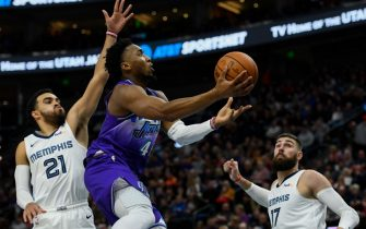 SALT LAKE CITY, UT - DECEMBER 07: Donovan Mitchell #45 of the Utah Jazz shoots over Tyus Jones #21 and Jonas Valanciunas #17 of the Memphis Grizzlies during a game at Vivint Smart Home Arena on December 7, 2019 in Salt Lake City, Utah. NOTE TO USER: User expressly acknowledges and agrees that, by downloading and/or using this photograph, user is consenting to the terms and conditions of the Getty Images License Agreement.  (Photo by Alex Goodlett/Getty Images)