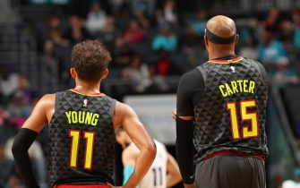 CHARLOTTE, NC - DECEMBER 8: Trae Young #11 of the Atlanta Hawks and Vince Carter #15 of the Atlanta Hawks looks on against the Charlotte Hornets on December 8, 2019 at Spectrum Center in Charlotte, North Carolina. NOTE TO USER: User expressly acknowledges and agrees that, by downloading and or using this photograph, User is consenting to the terms and conditions of the Getty Images License Agreement.  Mandatory Copyright Notice: Copyright 2019 NBAE (Photo by Brock Williams-Smith/NBAE via Getty Images)