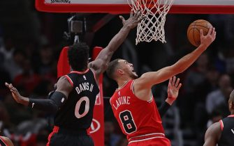 CHICAGO, ILLINOIS - DECEMBER 09: Zach LaVine #8 of the Chicago Bulls lays in a shot past Terence Davis #0 of the Toronto Raptors  at the United Center on December 09, 2019 in Chicago, Illinois. NOTE TO USER: User expressly acknowledges and agrees that , by downloading and or using this photograph, User is consenting to the terms and conditions of the Getty Images License Agreement. (Photo by Jonathan Daniel/Getty Images)
