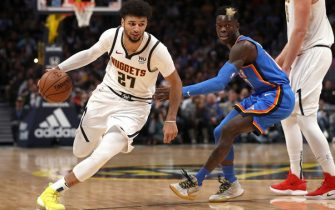 DENVER, COLORADO - DECEMBER 14: Jamal Murray #27 of the Denver Nuggets drives past Dennis Schroder #17 of the Oklahoma City Thunder off a pick set by Nikola Jokic #15 in the fourth quarter at Pepsi Center on December 14, 2019 in Denver, Colorado. NOTE TO USER: User expressly acknowledges and agrees that, by downloading and or using this photograph, User is consenting to the terms and conditions of the Getty Images License Agreement. (Photo by Matthew Stockman/Getty Images)