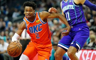 CHARLOTTE, NORTH CAROLINA - DECEMBER 27: Shai Gilgeous-Alexander #2 of the Oklahoma City Thunder dribbles the ball around Cody Martin #11 of the Charlotte Hornets during the first quarter during their game at the Spectrum Center on December 27, 2019 in Charlotte, North Carolina. NOTE TO USER: User expressly acknowledges and agrees that, by downloading and/or using this photograph, user is consenting to the terms and conditions of the Getty Images License Agreement. (Photo by Jacob Kupferman/Getty Images)