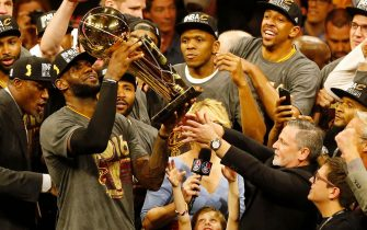 TOPSHOT - Cleveland Cavaliers forward LeBron James hoists the Larry O'Brien trophy after defeating the Golden State Warriors to win the NBA Finals on June 19, 2016 in Oakland, California. Powered by an amazing effort from LeBron James, the Cleveland Cavaliers completed the greatest comeback in NBA Finals history, dethroning defending champion Golden State 93-89 to capture their first NBA title. The Cavaliers won the best-of-seven series 4-3 to claim the first league crown in their 46-season history and deliver the first major sports champion to Cleveland since the 1964 NFL Browns, ending the longest such title drought for any American city.  / AFP / Beck Diefenbach        (Photo credit should read BECK DIEFENBACH/AFP via Getty Images)