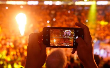 OAKLAND, CALIFORNIA - JUNE 07: A fan uses his iPhone to take a photo of player introductions prior to Game Four of the 2019 NBA Finals between the Golden State Warriors and the Toronto Raptors at ORACLE Arena on June 07, 2019 in Oakland, California. NOTE TO USER: User expressly acknowledges and agrees that, by downloading and or using this photograph, User is consenting to the terms and conditions of the Getty Images License Agreement. (Photo by Lachlan Cunningham/Getty Images)