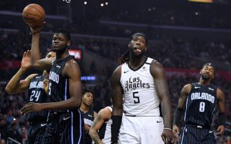 LOS ANGELES, CALIFORNIA - JANUARY 16:  Montrezl Harrell #5 of the LA Clippers reacts after his basket between Mo Bamba #5 and Terrence Ross #8 of the Orlando Magic during the first half at Staples Center on January 16, 2020 in Los Angeles, California. (Photo by Harry How/Getty Images)  NOTE TO USER: User expressly acknowledges and agrees that, by downloading and or using this photograph, User is consenting to the terms and conditions of the Getty Images License Agreement.