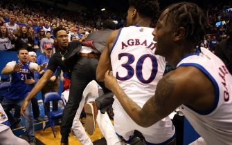 LAWRENCE, KANSAS - JANUARY 21:  A coach comes between James Love III #21 of the Kansas State Wildcats and Ochai Agbaji #30 and Marcus Garrett #0 of the Kansas Jayhawks during a brawl at the end of the game at Allen Fieldhouse on January 21, 2020 in Lawrence, Kansas. (Photo by Jamie Squire/Getty Images)