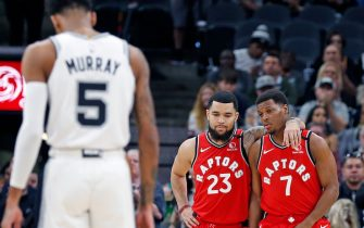 """SAN ANTONIO, TX - JANUARY 26:  After the first two possessions both teams took planned turnovers as the crowd chanted """"KOBE"""" as Fred VanVleet #23 of the Toronto Raptors and Kyle Lowry #7 embrace as Dejounte Murray #5 of the San Antonio Spurs takes a moment during first half action at AT&T Center on January 26, 2020 in San Antonio, Texas.  NOTE TO USER: User expressly acknowledges and agrees that ,by downloading and or using this photograph, User is consenting to the terms and conditions of the Getty Images License Agreement. (Photo by Ronald Cortes/Getty Images)"""