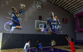 "Children play basketball at the ""House of Kobe"" gym, built in honour of former Los Angeles Lakers basketball player Kobe Bryant's 2016 visit to the Philippines, in Manila on January 27, 2020. - NBA legend Kobe Bryant died on January 26 when a helicopter he was riding in crashed and burst into flames in thick fog, killing all nine people on board including his teenage daughter and plunging legions of fans around the world into mourning. (Photo by Maria TAN / AFP) (Photo by MARIA TAN/AFP via Getty Images)"