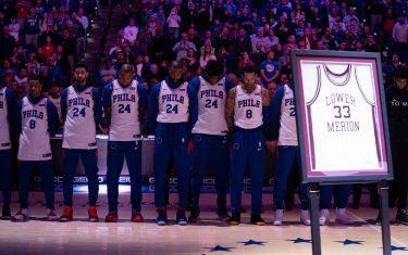 PHILADELPHIA, PA - JANUARY 28: Members of the Philadelphia 76ers stand for the national anthem prior to the game against the Golden State Warriors behind the Lower Merion High School jersey of former Los Angeles Laker star Kobe Bryant, who was killed in a helicopter crash, at the Wells Fargo Center on January 28, 2020 in Philadelphia, Pennsylvania. NOTE TO USER: User expressly acknowledges and agrees that, by downloading and/or using this photograph, user is consenting to the terms and conditions of the Getty Images License Agreement. (Photo by Mitchell Leff/Getty Images)