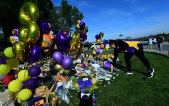 Laker fan Krystle Tamayo places a bouquet of flowers among other momentos at a makeshift memorial outside the gated community to the late NBA great Kobe Bryant's home in Newport Beach, California, on January 28, 2020. - The bodies of all nine people aboard the helicopter that crashed near Los Angeles killing NBA legend Kobe Bryant have been recovered, the coroner's office said Tuesday. Three bodies were retrieved from the wreckage by a special response team Sunday, and the remaining six on Monday, it said. (Photo by Frederic J. BROWN / AFP) (Photo by FREDERIC J. BROWN/AFP via Getty Images)