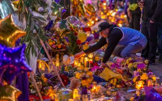 "LOS ANGELES, CA - JANUARY 28: A man places a hat at a makeshift memorial near Staples Center in remembrance of former NBA great Kobe Bryant who, along with his 13-year-old daughter Gianna, died January 26 in a helicopter crash, on January 28, 2020 in Los Angeles, California. Kobe and ""Gigi"" were among nine people killed in the crash in Calabasas, California as they were flying to his Mamba Sports Academy in Thousand Oaks, where he was going to coach her in a tournament game.  (Photo by David McNew/Getty Images)"