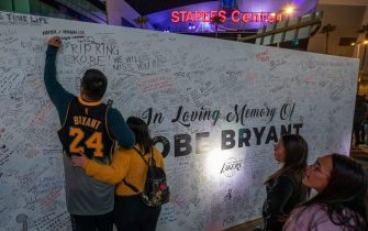 "LOS ANGELES, CA - JANUARY 28:  A fan signs a memorial wall near Staples Center in remembrance of former NBA great Kobe Bryant who, along with his 13-year-old daughter Gianna, died January 26 in a helicopter crash, on January 28, 2020 in Los Angeles, California. Kobe and ""Gigi"" were among nine people killed in the crash in Calabasas, California as they were flying to his Mamba Sports Academy in Thousand Oaks, where he was going to coach her in a tournament game.  (Photo by David McNew/Getty Images)"