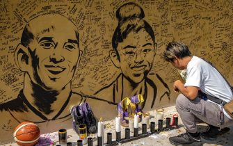 """VALENZUELA, PHILIPPINES - JANUARY 28: A basketball fan lights a candle next to a mural of former NBA star Kobe Bryant and his daughter Gianna outside the """"House of Kobe"""" basketball court on January 28, 2020 in Valenzuela, Metro Manila, Philippines. Bryant, who is hugely popular in basketball-obsessed Philippines, perished in a helicopter crash on January 26, 2020 in Calabasas, California. He died together with his 13-year-old daughter Gianna and seven others. (Photo by Ezra Acayan/Getty Images)"""