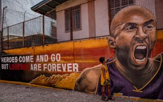 """VALENZUELA, PHILIPPINES - JANUARY 28: A child stands next to a mural of former NBA star Kobe Bryant outside the """"House of Kobe"""" basketball court on January 28, 2020 in Valenzuela, Metro Manila, Philippines. Bryant, who is hugely popular in basketball-obsessed Philippines, perished in a helicopter crash on January 26, 2020 in Calabasas, California. He died together with his 13-year-old daughter Gianna and seven others. (Photo by Ezra Acayan/Getty Images)"""
