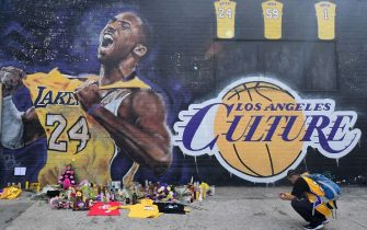 People gather in front of a Kobe Bryant mural in downtown Los Angeles on January 27, 2020. - Nine people were killed in the helicopter crash which claimed the life of NBA star Kobe Bryant and his 13 year old daughter, Los Angeles officials confirmed on Sunday. Los Angeles County Sheriff Alex Villanueva said eight passengers and the pilot of the aircraft died in the accident. The helicopter crashed in foggy weather in the Los Angeles suburb of Calabasas. Authorities said firefighters received a call shortly at 9:47 am about the crash, which caused a brush fire on a hillside. (Photo by FREDERIC J. BROWN / AFP) (Photo by FREDERIC J. BROWN/AFP via Getty Images)