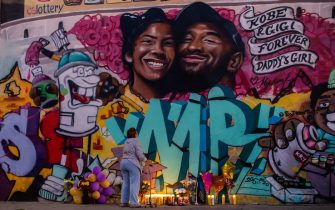 TOPSHOT - A woman looks at a mural by the artists Muck Rock and Mr79lts showing Kobe Bryant and his daughter Gianna Bryant, who were killed with seven others in a helicopter crash on January 26, in Los Angeles on January 27, 2020. - Federal investigators sifted through the wreckage of the helicopter crash that killed basketball legend Kobe Bryant and eight other people, hoping to find clues to what caused the accident that stunned the world. (Photo by Apu GOMES / AFP) / RESTRICTED TO EDITORIAL USE - MANDATORY MENTION OF THE ARTIST UPON PUBLICATION - TO ILLUSTRATE THE EVENT AS SPECIFIED IN THE CAPTION (Photo by APU GOMES/AFP via Getty Images)