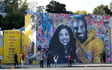 People stop to take pictures in front of the new mural by French artist Mr. Brainwash picturing Kobe Bryant and his daughter Gigi in Los Angeles on January 31, 2020. (Photo by Chris Delmas / AFP) / RESTRICTED TO EDITORIAL USE - MANDATORY MENTION OF THE ARTIST UPON PUBLICATION - TO ILLUSTRATE THE EVENT AS SPECIFIED IN THE CAPTION (Photo by CHRIS DELMAS/AFP via Getty Images)