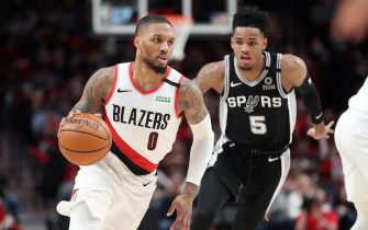 PORTLAND, OREGON - FEBRUARY 06: Damian Lillard #0 of the Portland Trail Blazers dribbles against Dejounte Murray #5 of the San Antonio Spurs in the third quarter during their game at Moda Center on February 06, 2020 in Portland, Oregon. NOTE TO USER: User expressly acknowledges and agrees that, by downloading and or using this photograph, User is consenting to the terms and conditions of the Getty Images License Agreement. (Photo by Abbie Parr/Getty Images)
