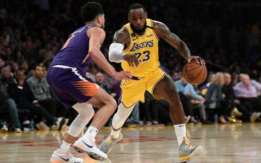 LOS ANGELES, CA - FEBRUARY 10:  LeBron James #23 of the Los Angeles Lakers drives against Devin Booker #1 of the Phoenix Suns during the first half at Staples Center on February 10, 2020 in Los Angeles, California. NOTE TO USER: User expressly acknowledges and agrees that, by downloading and/or using this Photograph, user is consenting to the terms and conditions of the Getty Images License Agreement. (Photo by Kevork Djansezian/Getty Images)
