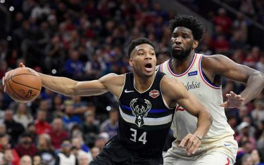 PHILADELPHIA, PENNSYLVANIA - DECEMBER 25: Giannis Antetokounmpo #34 of the Milwaukee Bucks looks to pass as Joel Embiid #21 of the Philadelphia 76ers defends during the first half of the game at Wells Fargo Center on December 25, 2019 in Philadelphia, Pennsylvania. NOTE TO USER: User expressly acknowledges and agrees that, by downloading and or using this photograph, User is consenting to the terms and conditions of the Getty Images License Agreement. (Photo by Sarah Stier/Getty Images)
