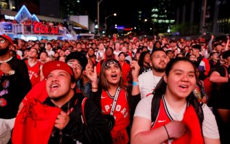 TORONTO, ON - JUNE 07: Toronto Raptors fans cheer as they gather to watch Game 4 of the NBA Finals series outside Scotiabank Arena at 'Jurassic Park', on June 7, 2019 in Toronto, Canada. (Photo by Cole Burston/Getty Images)
