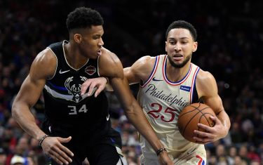 PHILADELPHIA, PENNSYLVANIA - DECEMBER 25: Ben Simmons #25 of the Philadelphia 76ers dribbles the ball as Giannis Antetokounmpo #34 of the Milwaukee Bucks defends during the second half of the game at Wells Fargo Center on December 25, 2019 in Philadelphia, Pennsylvania. NOTE TO USER: User expressly acknowledges and agrees that, by downloading and or using this photograph, User is consenting to the terms and conditions of the Getty Images License Agreement. (Photo by Sarah Stier/Getty Images)