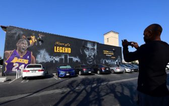 A passerby stops to photograph a huge mural in honour of the late Kobe Bryant by artist PeQue Brown in the south Los Angeles, California neighborhood of Watts on February 14, 2020, a day after it was unveiled. - The 65 x 28 foot mural features multiple images of Bryant, including one with his daughter and the names of all the victims of the fateful January 26 helicopter crash. The former Los Angeles Laker and NBA star was buried in a private ceremony with his daughter on February 7 with a Kobe Bryant Memorial set for Monday February 24 at Staples Center. (Photo by Frederic J. BROWN / AFP) (Photo by FREDERIC J. BROWN/AFP via Getty Images)