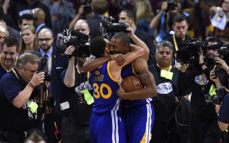 Golden State Warriors Stephen Curry (L) and MVP Andre Iguodala (R) celebrate their team defeating the Cleveland Cavaliers in Game 6 to win the 2015 NBA Finals June 16, 2015 at the Quicken Loans Arena in Cleveland, Ohio.  Curry and Iguodala each scored 25 points as the Golden State Warriors captured their first NBA title in 40 years by defeating Cleveland 105-97 to win the NBA Finals.    AFP PHOTO  / TIMOTHY A. CLARY        (Photo credit should read TIMOTHY A. CLARY/AFP via Getty Images)