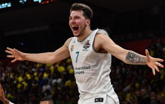 Real Madrid's Slovenian Luka Doncic (C-7) jumps over the barrier as the team celebrates their 85-80 win over Fenerbahce in the Euroleague Final Four finals basketball match between Real Madrid and Fenerbahce Dogus Istanbul at The Stark Arena in Belgrade on May 20, 2018. (Photo by Andrej ISAKOVIC / AFP)        (Photo credit should read ANDREJ ISAKOVIC/AFP via Getty Images)
