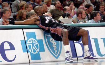 CHARLOTTE, NC - DECEMBER 2:  Utah Jazz's Karl Malone stretches at the scorer's table before entering the game during the second half of the, 02 December 2000, game against the Charlotte Hornets at Charlotte Coliseum in Charlotte, NC.  Malone is on the verge of passing Wilt Chamberlain for second place on the NBA all-time scoring list. Kareem Abdul-Jabbar is first in all-time scoring. Charlotte won the game 94-89.  (Photo credit should read ERIK PEREL/AFP via Getty Images)