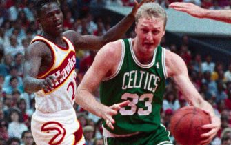 (Original Caption) Celtics' forward Larry Bird (right) goes to the basket over Hawks center Tree Rollins (left) for two points during second period action here 5/20.