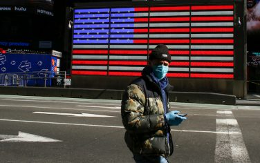 A man wears a face mask as he check his phone in Times Square on March 22, 2020 in New York City. - Coronavirus deaths soared across the United States and Europe on despite heightened restrictions as hospitals scrambled to find ventilators. (Photo by Kena Betancur / AFP) (Photo by KENA BETANCUR/AFP via Getty Images)