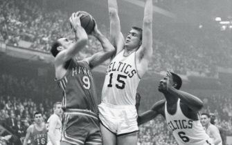 (Original Caption) Leaps to Block. Boston: Tommy Heinsohn (15), of the Boston Celtics, leaps high to block a shot by Bob Petit (9) of the St. Louis Hawks, during their game at the Boston Garden here. Bill Russell (right) of the Celtics, gets ready to leap for the rebound. The Celtics won, 140-122.
