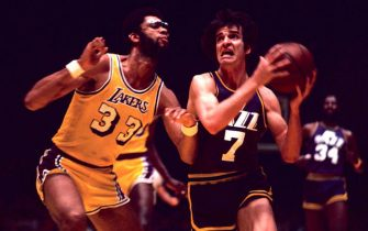 "LOS ANGELES, CA - FEBRUARY 13:   ""Pistol"" Pete Maravich, Guard of the New Orleans Jazz, drives to the basket while being guarded by Kareem Abdul-Jabbar of the Los Angeles Lakers during an NBA basketball game at The Forum on February 13, 1976. Maravich scored 30 points. The Lakers defeated the Jazz 126-112. (Photo by Ross Lewis/Getty Images)."