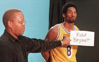 LOS ANGELES, UNITED STATES:  Los Angeles Lakers' player Kobe Bryant (R), poses for video footage as a television technician holds up a card with his name, 27 January during Media Day at the Forum. Bryant, one of the youngest players in the NBA, is considered a possible future successor to Michael Jordan. AFP PHOTO/Mike NELSON (Photo credit should read MIKE NELSON/AFP via Getty Images)