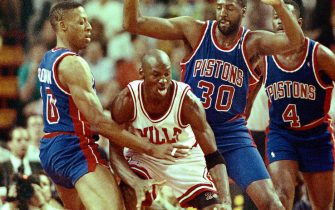 (Original Caption) Pistons' Dennis Rodman; Tree Rollins (30) and Joe Dumars surround Bulls' Michael Jordan during the 3rd quarter 5/21 of game two of the Eastern Conference finals.