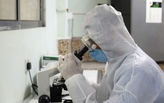 An employee, wearing his personal protective equipment (PPE), looks through a microscope at the newly-inaugurated laboratory for coronavirus testing in Yemen's third city of Taiz, on April 30, 2020. - Yemen's healthcare system has been blighted by years of war that have driven millions from their homes and plunged the country into what the United Nations describes as the world's worst humanitarian crisis. (Photo by AHMAD AL-BASHA / AFP) (Photo by AHMAD AL-BASHA/AFP via Getty Images)