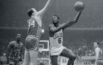 Boston Celtics' player Bill Russell hooks a shot during the NBA championship's final game in 1960 against the Saint Louis Hawks.