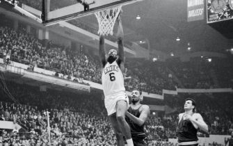(Original Caption) Bill Russell soars high to dunk in two points, beating out 76ers' Wilt Chamberlain and Dave Gambee during fourth quarter action at the Boston Gardens. Celtics won game, 133-111.